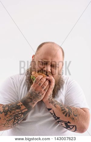 Fat man is biting burger with appetite. His eyes are closed with enjoyment. Isolated