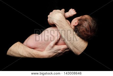 Safety concept - baby in comfort father's hands (shallow depth of field)