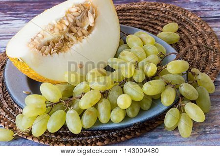 A piece of melon and a bunch of ripe grapes on a metal plate on old wooden table.