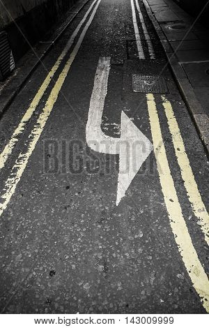 Left turn arrow painted on an asphalt street between double yellow lines on a narrow urban road with vignetting