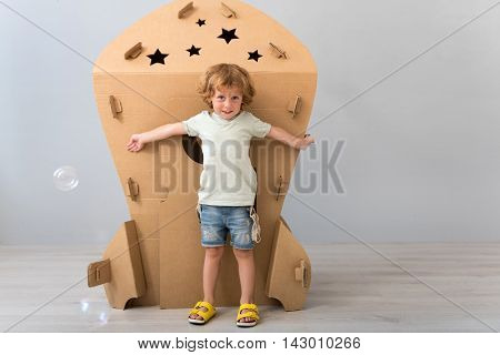 So big rocket. Cute little boy standing in front of a big carton rocket with hands open and looking at the camera on the grey background