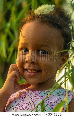 Portrait of a black baby girl close-up. Baby smiles among the leaves