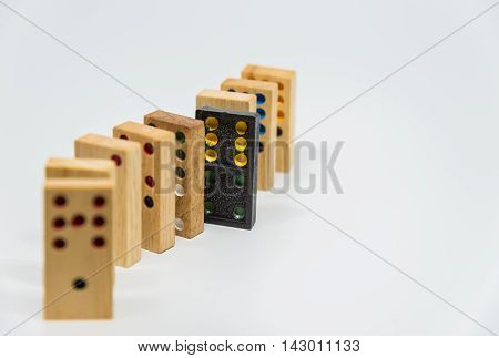 Wooden dominoes sequence with black plastic domino on white background with selective focus