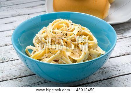 Fettuccine Alfredo classic Italian Pasta on a white wood beach table.