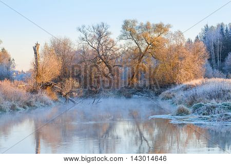 Winter landscape with a steaming river on frost and trees covered with hoar