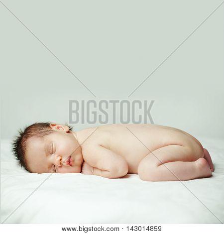 Little baby cute sleeping newborn on gray