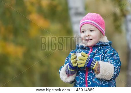 Autumn outdoor head and shoulders portrait of little girl is holding steel thermos flask cup in hands