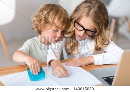 Time together. Serious little girl with glasses drawing in the notebook while the little charming boy sitting near her in front of the laptop