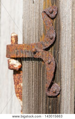 Vintage rusted metal door hinge over the weathered wooden wall.
