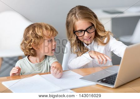 Have a look. Beautiful little girl with glasses showing something to the interested little child while pointing at the screen of the laptop