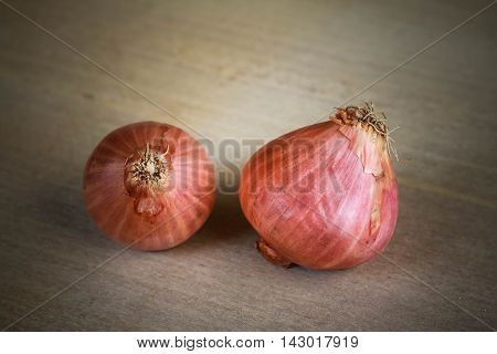 Shallots pile on wooden background in garden