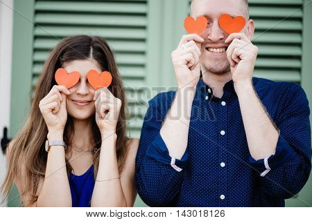 Young couple holding red heart symbol and having fun outdoor.