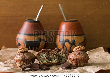 Bicolor muffin with chocolate, poppies and walnuts on paper and two gourds with yerba mate. Loving couple.