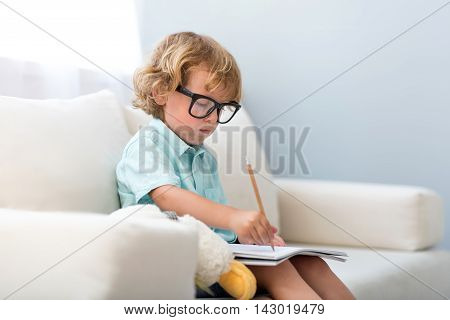 I have a dream. Little concentrated boy wearing glasses and drawing while sitting on the couch