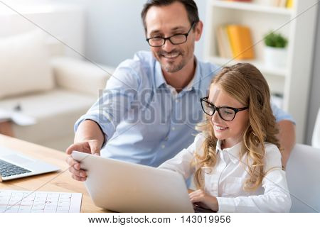 It is very easy. Contented mature man explaining to a little cute girl how to use a laptop while sitting at the table