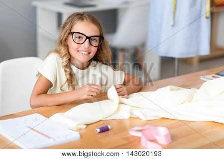I like it. Charming little girl with glasses tailoring and looking at the camera while sitting at the table