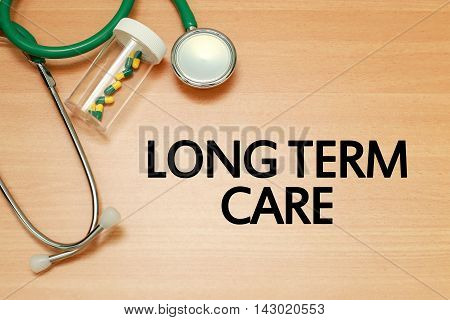 Medical concept - Stethoscope and pills on wood with Long term care word