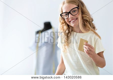 Easy even for a child. Adorable little girl holding a credit card while looking at the camera and sitting