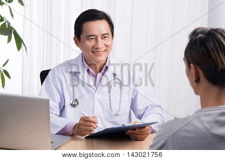 Confident asian male doctor discussing diagnosis with patient in office