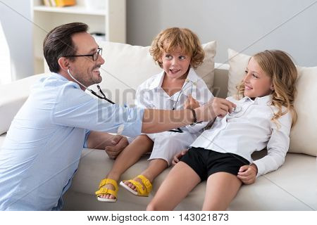 Your heart works. Delighted bearded man examining his smiling daughter with a stethoscope while little boy sitting near them and talking