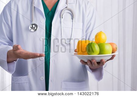 Nurse or male doctor giving fruits. Health care concept isolated on white background.