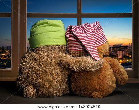 Two friends or fans to watch the sunset in the window. Toys colorful hats bear cubs. Embrace the window. Concept - love friendship support