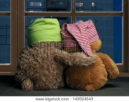 Two friends looking out the window at the windows of the house. Toys colorful hats bear cubs. Embrace the window. Concept - love friendship support evening together