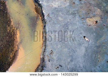 aerial photo of a naked woman lying on the ground next to the river in the zone of ecological disaster Karabash