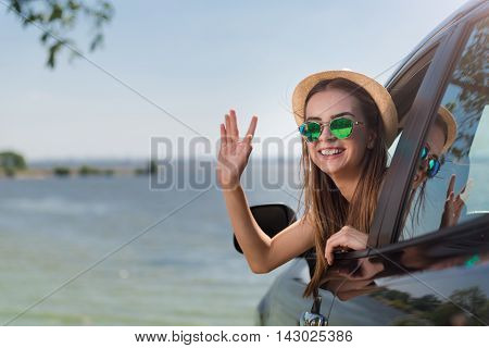 Brighten your life. Positive content, smiling beautiful woman sitting in the car and smiling while resting at the seaside