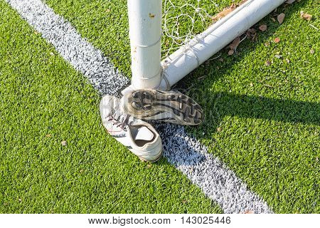 Old soccer Shoes on artificial turf field with goal