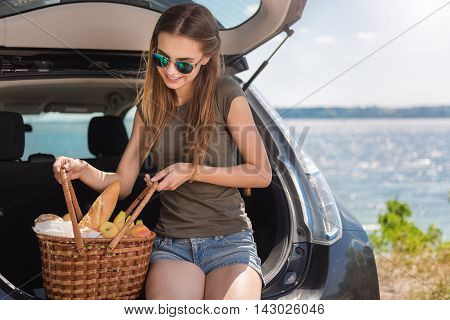 Ready for a picnic. Positive delighted smiling woman sitting in the bonnet of the car and holding basket with food while resting on the seaside
