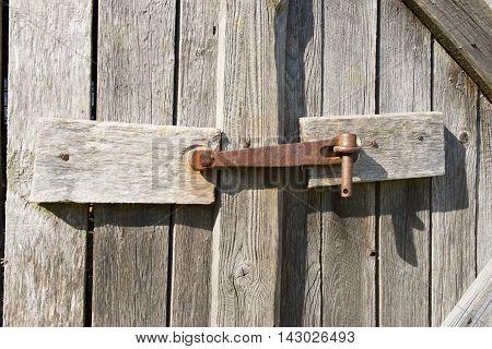 Old rusted metal barn door lock closeup.