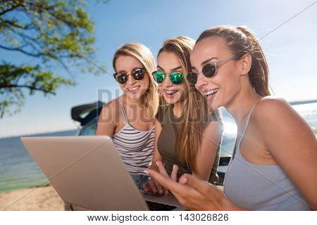 Modern generation. Positive delighted emotional friends standing on the beach near car and using laptop while expressing gladness