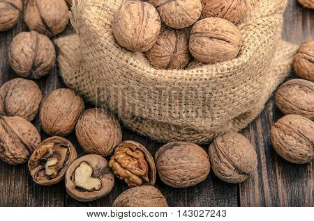 Walnut on a bag, on a wooden background