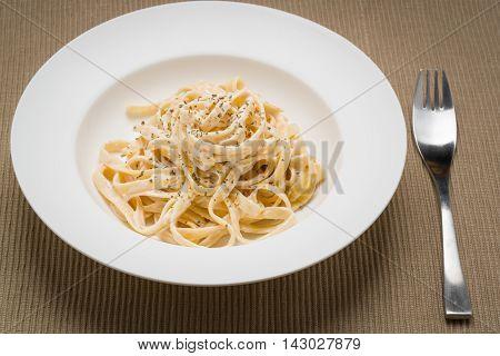 Fettuccine Alfredo classic Italian Pasta on a dark table.