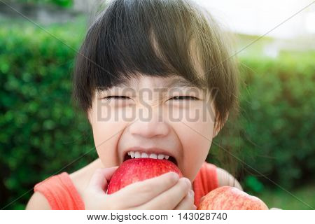 Funny food little girl with red Apple smiling happy. Healthy eating and vegetables concept photo