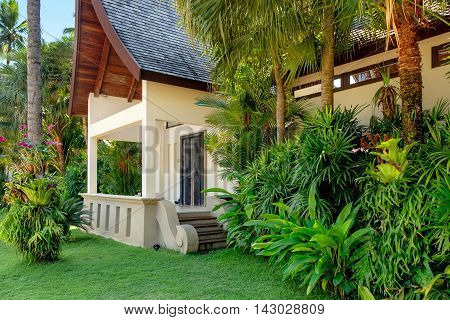 A typical small Thai house in the countryside with palm trees tropical plants and flowers and a bahia grass lawn Koh Chang Thailand