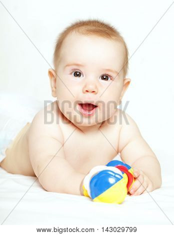 Happy child playing with ratte - baby 5 months old