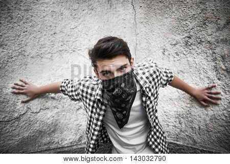 Gangster in black bandana near the wall