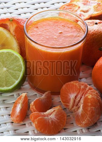 Freshly Squeezed Mixed Citrus Juice in Glass with Tangerines and Slices of Limes and Lemons closeup on Wicker background