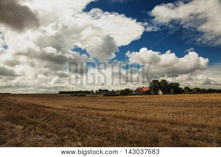 cloudy autumn sky over danish fields and houses