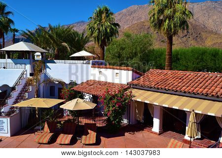 Courtyard patio with cabanas and outdoor furniture including lounge chairs and umbrellas and the San Jacinto Mountains beyond taken in Palm Springs, CA