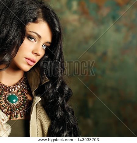 Beautiful fashion woman with curly hair and stage makeup on background