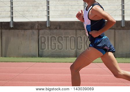 Athlete runner running on athletic track,side view