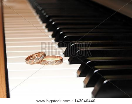 Gold wedding rings lie on the piano keys.