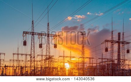 Silhouette of transformers over yellow sunset sky
