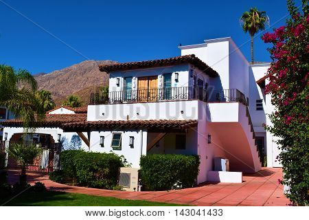 Spanish style Hacienda Villa surrounded by lush gardens with the San Jacinto Mountains beyond taken in Palm Springs, CA