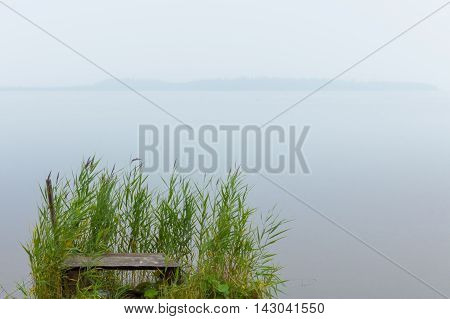 a small pier in the mist overgrown with reeds on the shore of Lake Zyuratkul Ural Russia