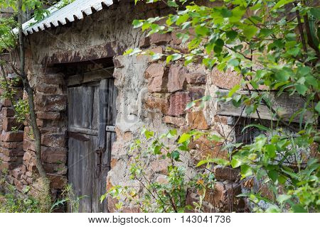 abandoned building of masonry with an old wooden door
