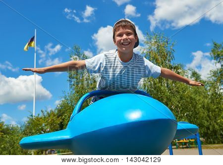 child fly on blue airplane attraction in park, happy childhood, summer vacation concept